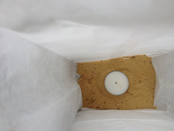 1/2 cup of sand or pebbles in bottom to keep bag from blowing away. Place candle into sand.  Lift wick up so it will be easy to light.
