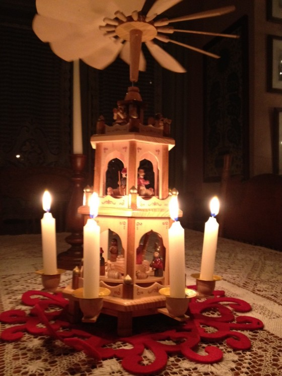 Wooden carousel on our kitchen table. Heat from the candles makes the tiers go around and around. It has Baby Jesus, Mary and Joseph inside along with  the wise men and angels