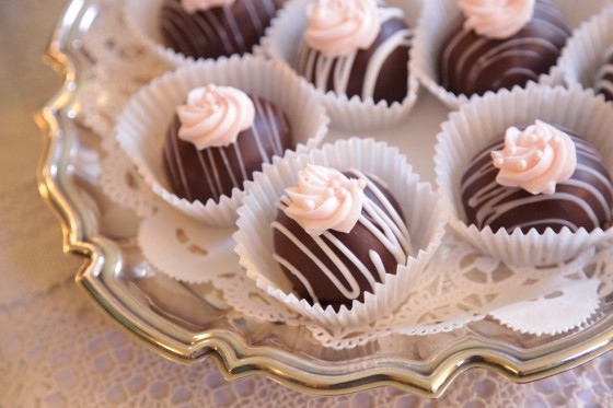 Buckeyes streaked with white glaze and topped with pink frosted rose